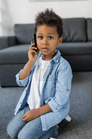 Photo for Cute afro boy talking by phone while sitting on floor on living room - Royalty Free Image