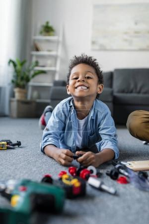 Photo for Adorable happy african-american boy with toy tools on floor - Royalty Free Image