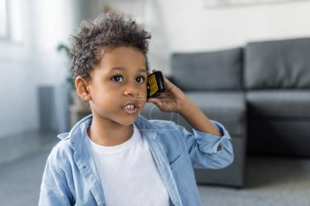 Photo for Beautiful afro boy talking by phone while sitting on floor on living room - Royalty Free Image