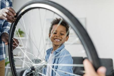 Photo for Happy smiling african-american boy behind bicycle wheel - Royalty Free Image