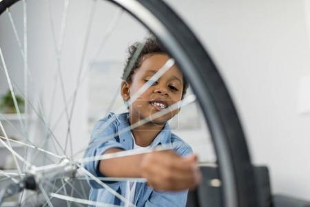 Photo for Adorable focused african-american boy repairing bicycle indoor - Royalty Free Image