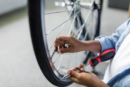Photo for Cropped shot of little afro boy repairing bicycle with screwdriver - Royalty Free Image