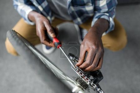 afro man repairing bicycle at home