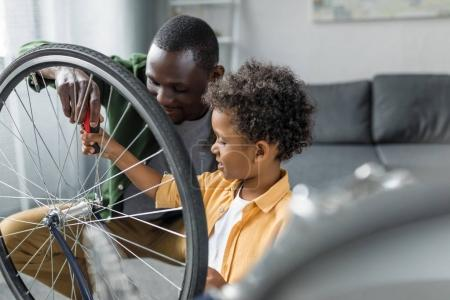 afro father and son repairing bicycle
