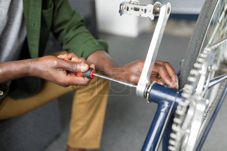 Black man repairing bicycle with screwdriver