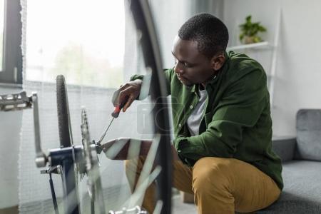 afro man repairing bicycle at home