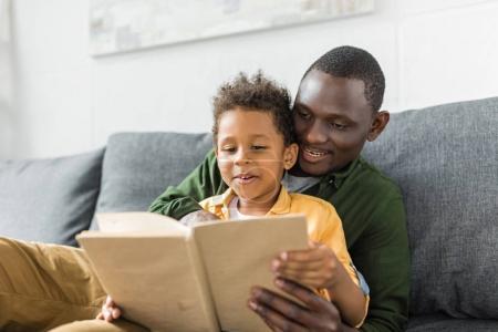 Photo pour Souriant afro-américain père et fils lecture livre ensemble - image libre de droit