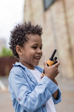 Photo for Cute smiling afro boy with portable radio set - Royalty Free Image