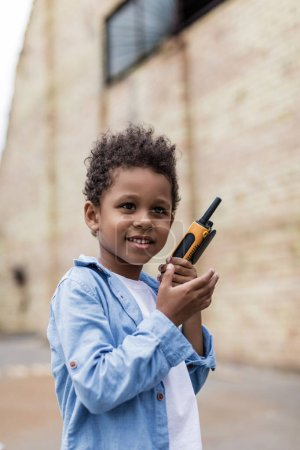 Photo for Beautiful smiling afro boy with portable radio set - Royalty Free Image