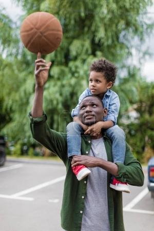 Father spinning ball with son on shouders
