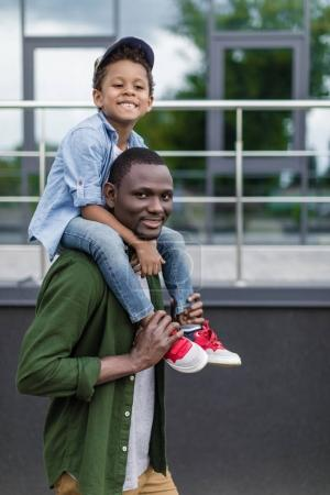 cute afro kid piggybacking on father