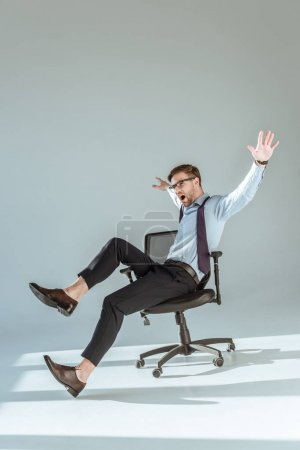 Excited stylish businessman sitting on chair with hands and legs outstretched