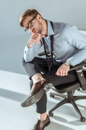 Young thoughtful businessman sitting on chair with hand on chin