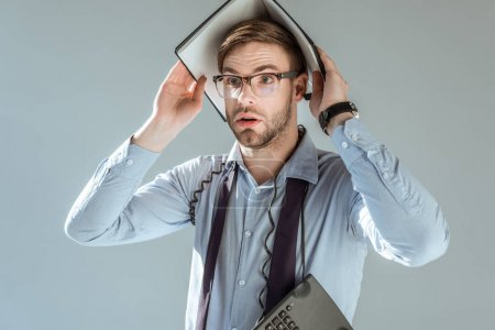 Photo for Young surprised businessman holding notebook on his head isolated on grey - Royalty Free Image