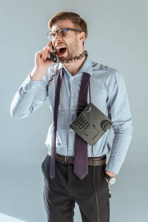 Young annoyed businessman screaming while talking on phone