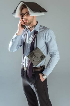 Confused businessman holding notebook on his head while talking on phone isolated on grey