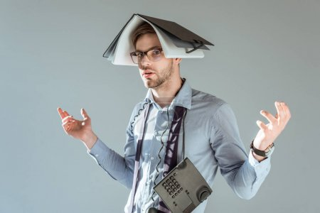 Young confused businessman holds notebook on his head and phone on neck isolated on grey