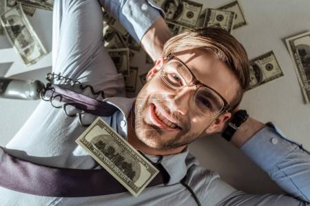 Young rich businessman lying on dollar bills