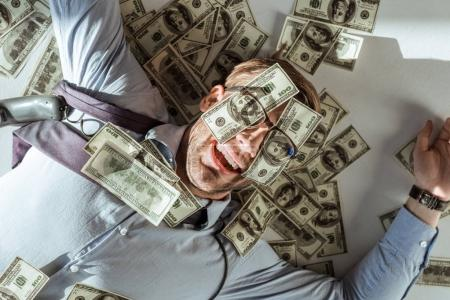Young happy rich businessman lying on floor with dollar bills covering his face