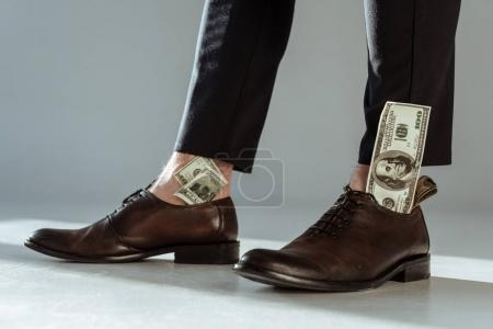 Close-up view of dollar bills in businessman's shoes