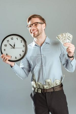 Young smiling businessman showing money and clock isolated on grey