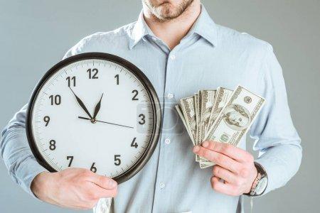 Photo pour Vue rapprochée de l'homme d'affaires montrant argent et horloge isolé sur fond gris - image libre de droit