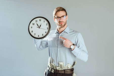 Young confident businessman pointing on clock isolated on grey