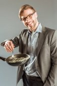 Young businessman frying dollar bills in pan isolated on grey