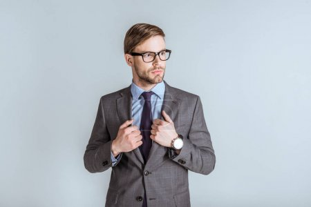 Young confident businessman in suit isolated on grey