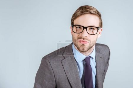Young concentrated businessman looking at camera isolated on grey