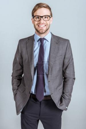 Young smiling businessman with hands in pockets isolated on grey