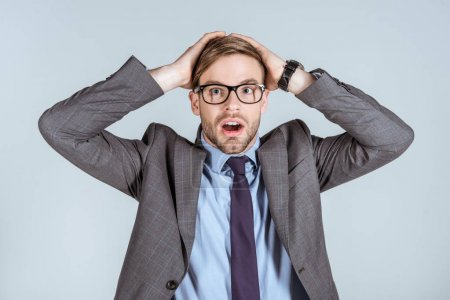 Young surprised businessman holding hands on head isolated on grey