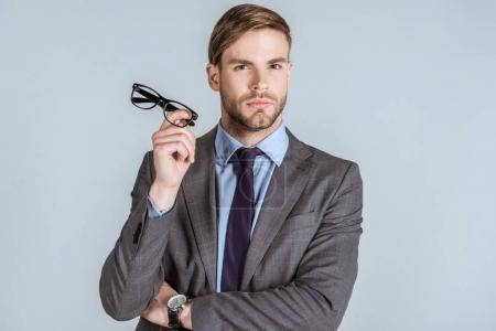 Photo for Young confident businessman holding glasses isolated on grey - Royalty Free Image