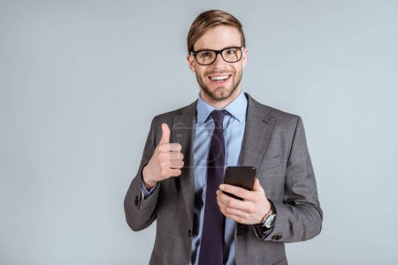 Young smiling businessman using smartphone and showing thumb up isolated on grey