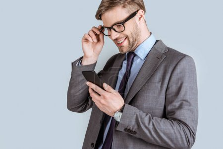 Photo for Young businessman looking at smartphone screen isolated on grey - Royalty Free Image