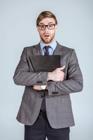 Young surprised businessman holding notebook isolated on grey