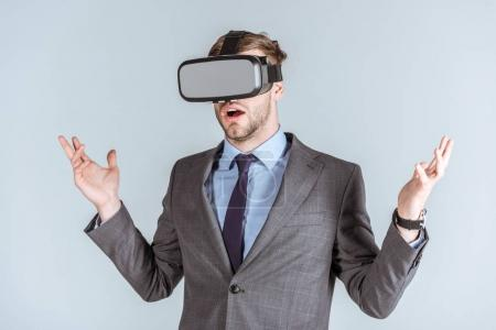 Young businessman using vr headset isolated on grey