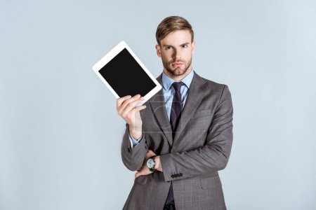 Young thoughtful businessman holding digital tablet isolated on grey