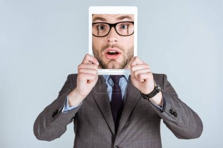 Young businessman holding digital tablet with his face on screen isolated on grey