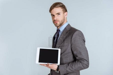 Young thoughtful businessman presenting digital tablet isolated on grey