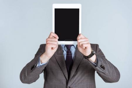Businessman holding digital tablet over his face isolated on grey