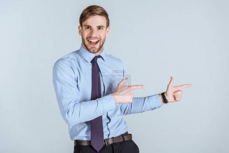 Young excited businessman pointing isolated on grey
