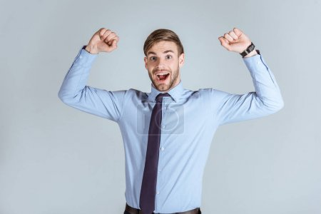 Photo for Young strong businessman raising arms up isolated on grey - Royalty Free Image