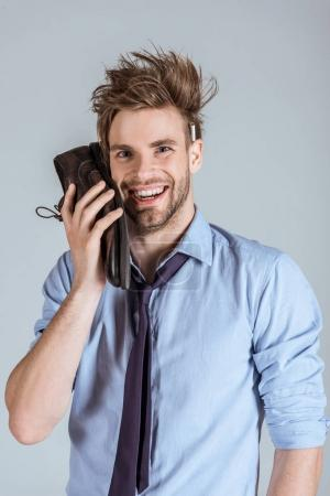 Overworking businessman with messy hair using shoe as phone isolated on grey