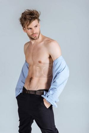 handsome businessman with messy hair taking off his shirt, isolated on grey
