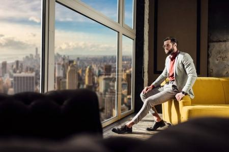 fashionable elegant man in stylish suit posing at window with city view