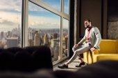 """Постер, картина, фотообои """"модный элегантный мужчина в стильный костюм позирует у окна с видом на город"""""""