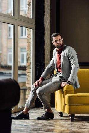 Photo for Stylish man in grey suit posing at window - Royalty Free Image