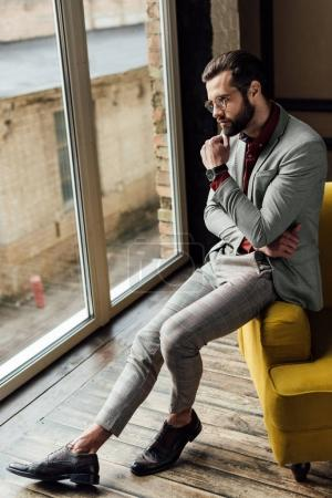 thoughtful man in trendy suit sitting at window