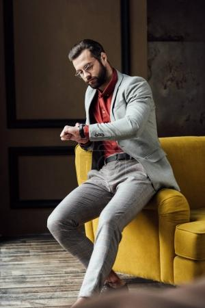 handsome bearded elegant man looking at watch